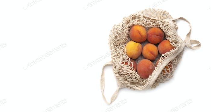 Saftige Pfirsiche voller Vitamine in kunststofffreiem Netzbeutel auf weiß isoliert