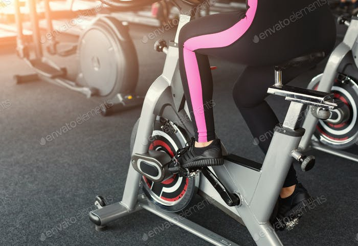 Woman's legs on exercise bikes in fitness club, healthy lifestyle