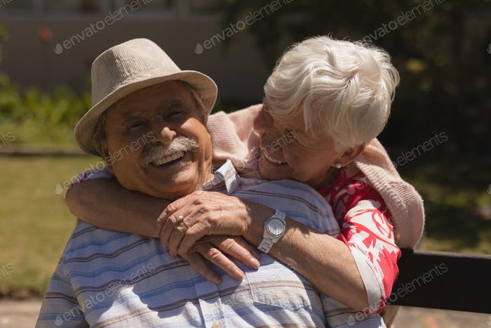 Front view of happy senior woman embracing senior man in garden