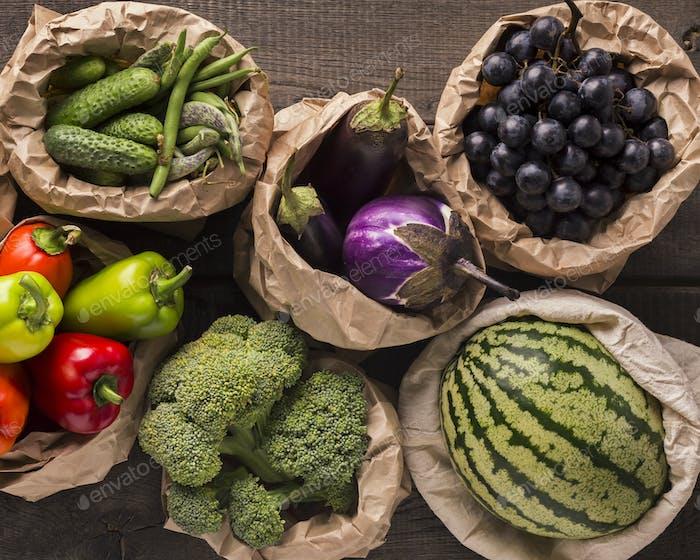 Frisches und ökologisches Obst und Gemüse in Natursäcken auf Holz