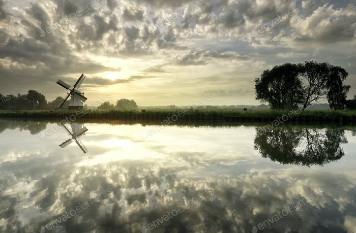 Dutch windmill and sky reflections in river at sundown