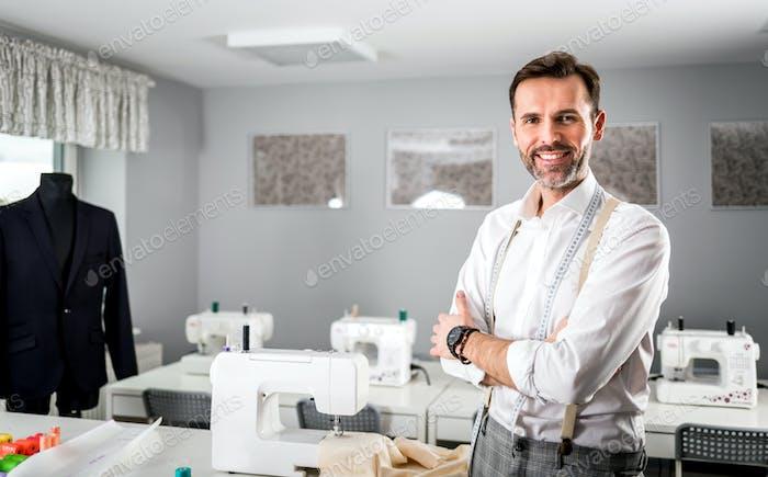 Smiling tailor shop owner standing above workshop desk, fashion design business