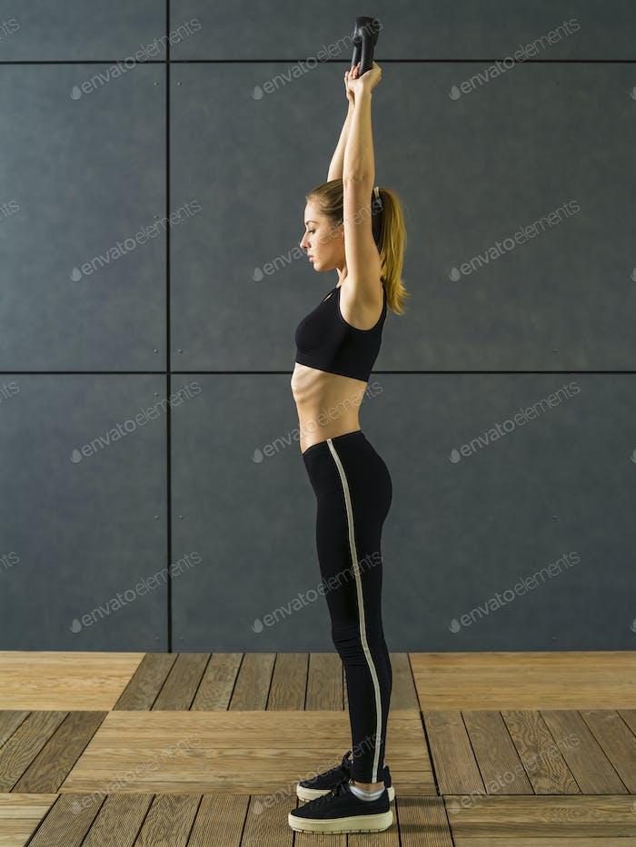 Junge Frau mit einem Kettlebell trainieren