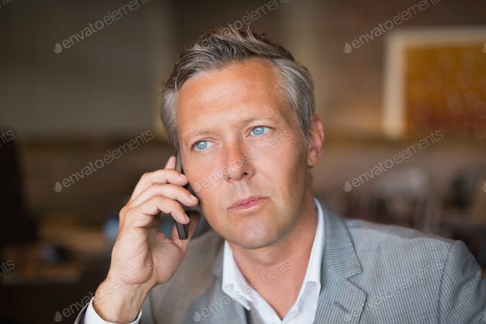 Handsome businessman on the phone at the cafe