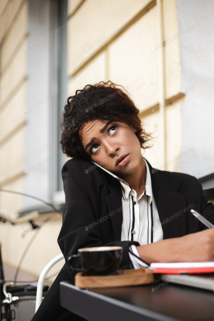 Thoughtful lady with dark curly hair working with cup of coffee on table