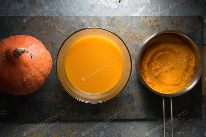 Pumpkin puree in a saucepan, pumpkin soup and pumpkin on a gray stone