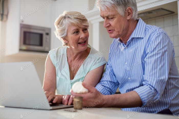 Senior couple checking medicine on laptop in kitchen