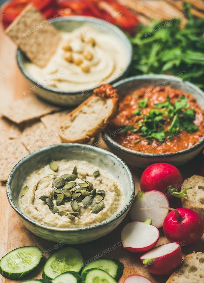 Vegetarian dips hummus, babaganush, muhammara over wooden background