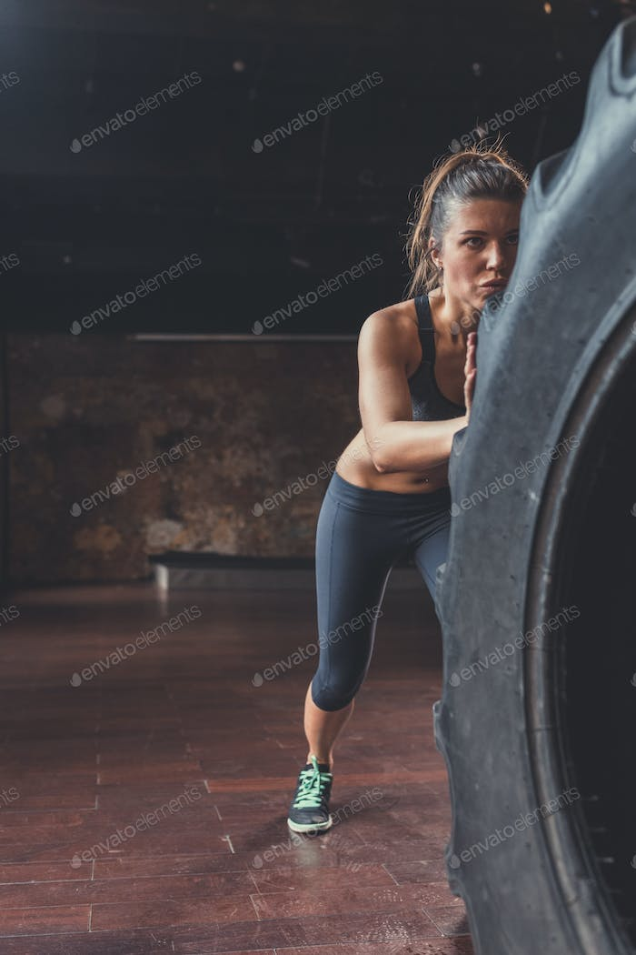 Young woman with a crossfit wheel