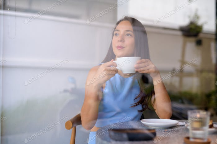 Young thoughtful businesswoman drinking coffee while looking through the window