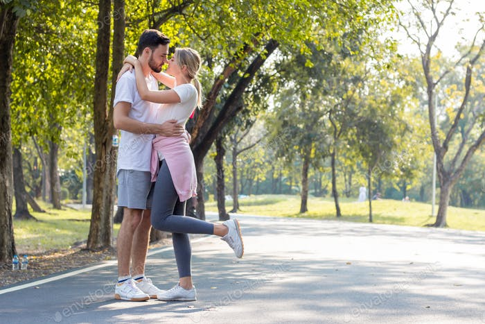 Couples standing kiss and hugging in the park.