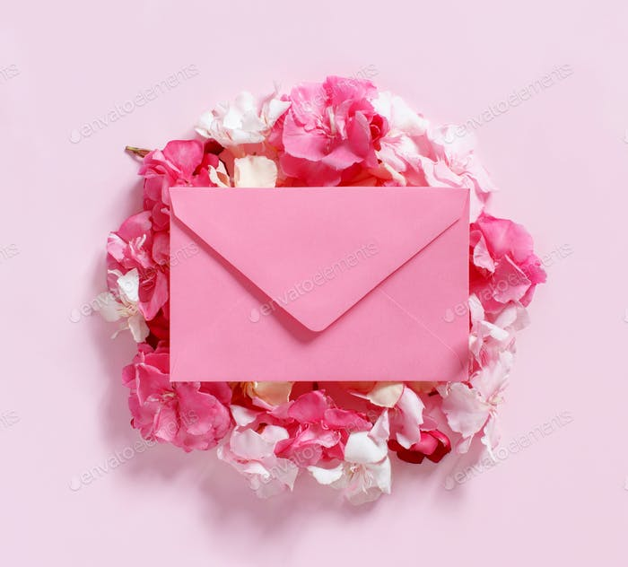 Pink envelope on flowers  over a pink background top view