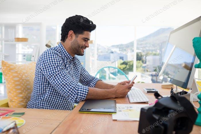 Graphic designer using mobile phone at desk