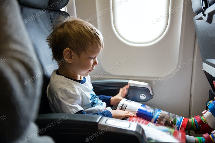 Little boy reading magazine while on board of airplane