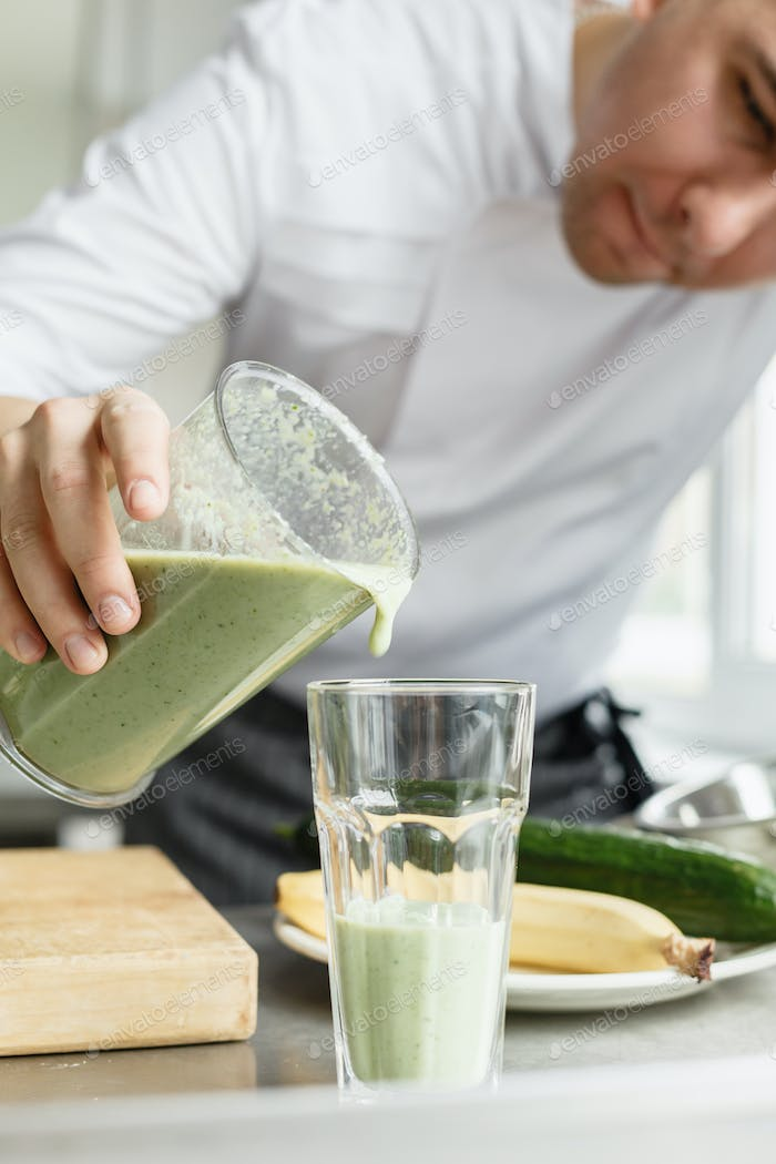 Male cooking fresh vegetable smoothie