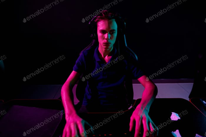 Young gamer playing in dark room