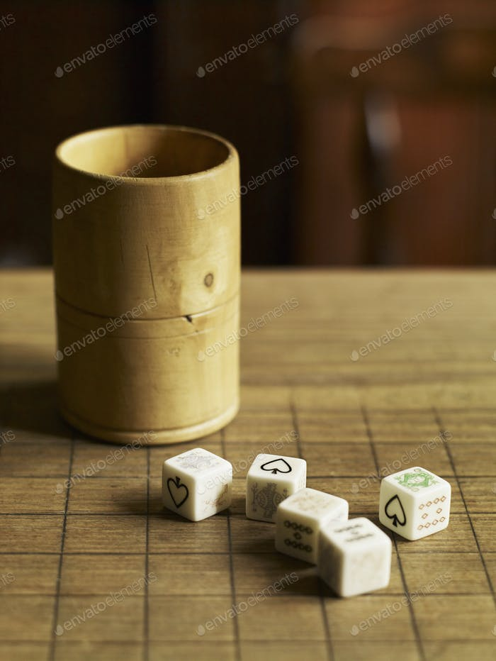 Five dice with printed faces, on a wooden pub table and a wooden cup beside them.