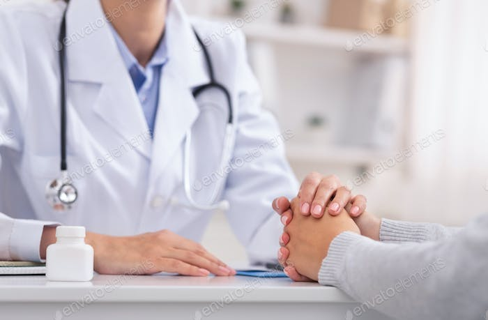 Unrecognizable Physician Comforting Female Patient Sitting In Office, Cropped