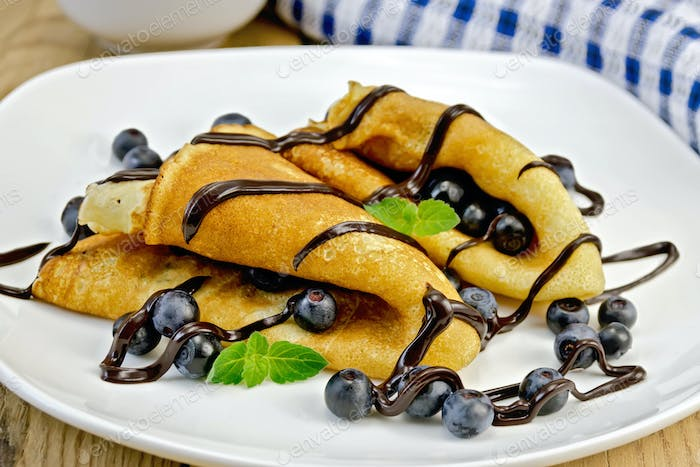 Pancakes with blueberries and chocolate syrup on the board