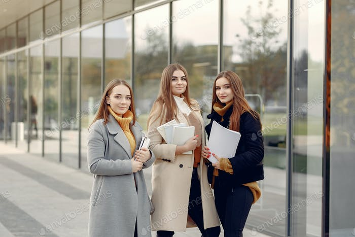 Young students on a student campus standing with a documents