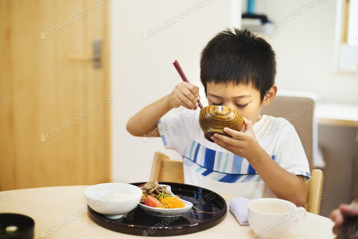 Family home. A boy eating a meal.
