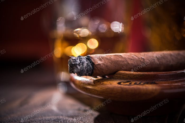 Smoking cigar in vintage ashtray