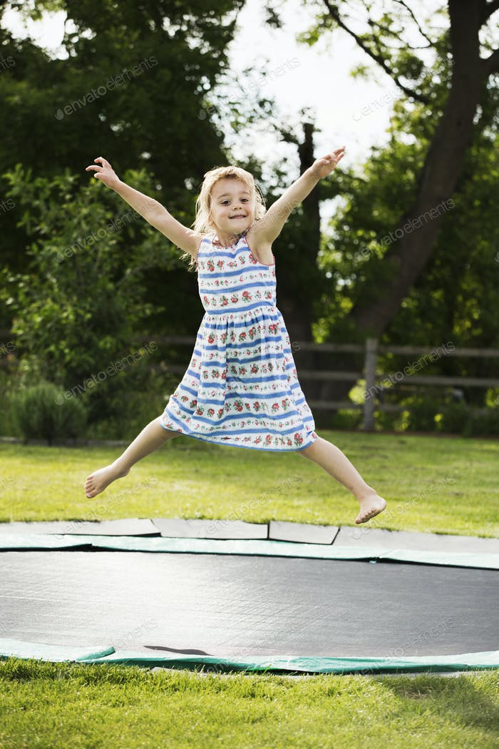 Girl in a sundress jumping on a trampoline set in the ground, in a garden.