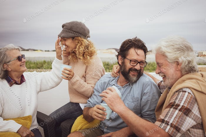 Family group of four people have fun and smile together outdoor on terrace