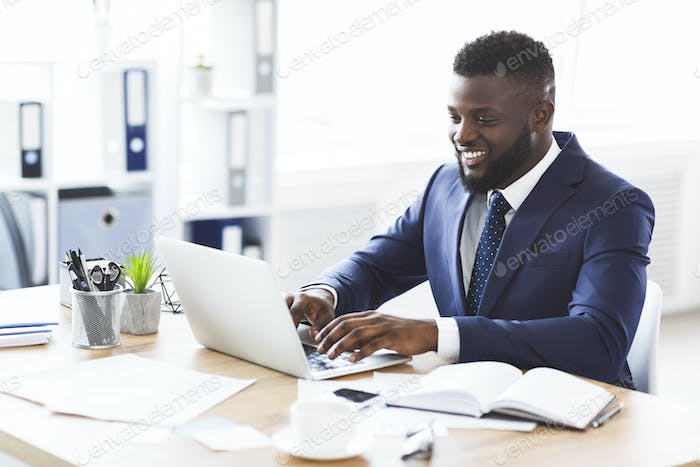 Happy young businessman working with laptop in office