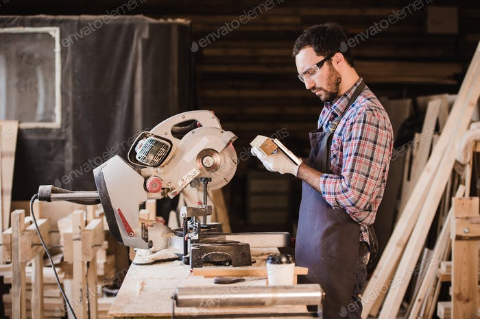 profession, carpentry, woodwork people concept - carpenter with wood plank and notebook checking his