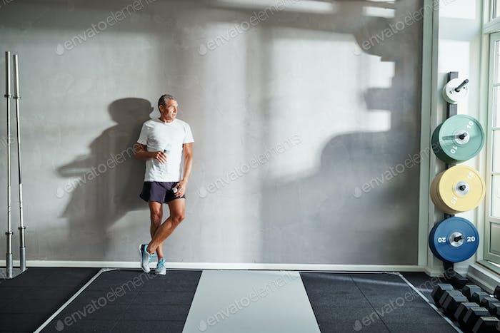 Reifer Mann Trinkwasser nach in einem Fitness-Studio Gewichtshaube