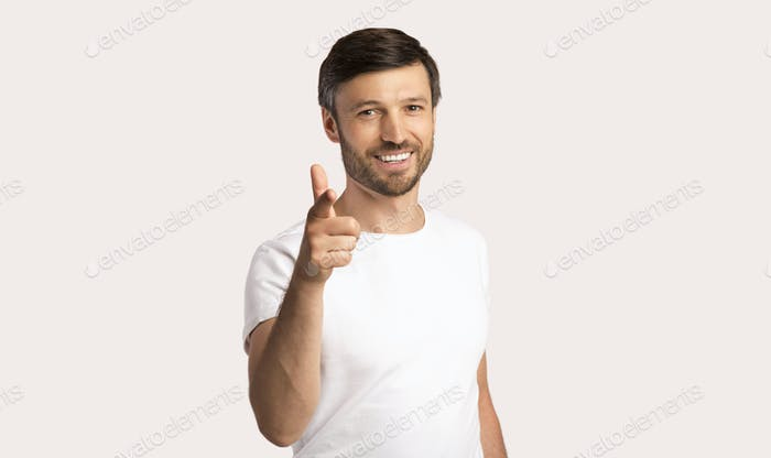 Smiling Guy Pointing Finger At Camera Standing In Studio