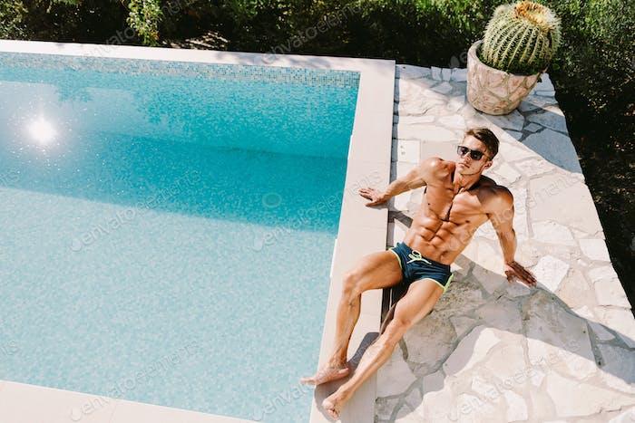 Sexy shirtless muskulösen Mann in Badehose entspannen und posieren in der Nähe von Schwimmbad im Freien