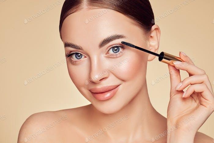 Beauty woman applying black mascara on eyelashes