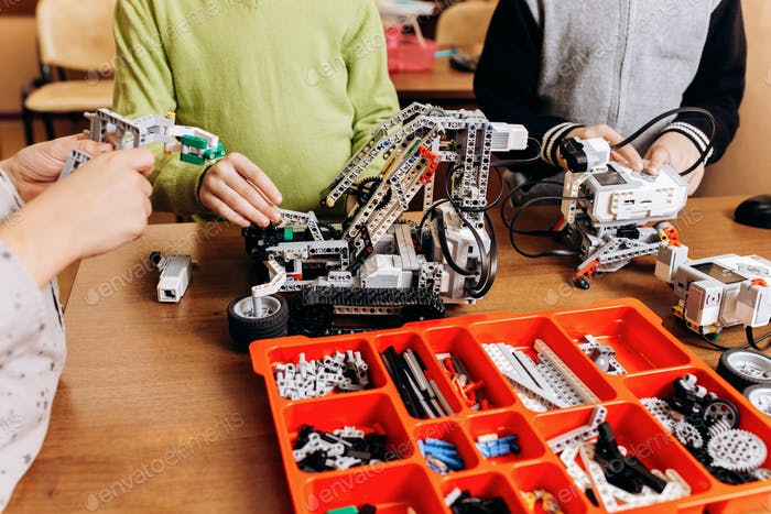 Three happy boys are making robots in the School of Robotics