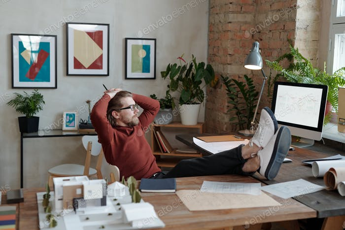 Relaxed architect looking at monitor with sketch