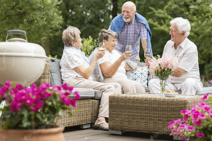 Two senior couples having a social gathering outside on a patio
