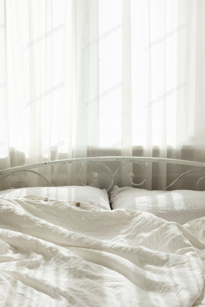 Beautiful morning light in bedroom. Pastel color white bedding