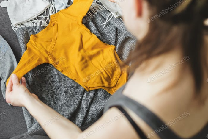 Young woman preparing clothes for baby