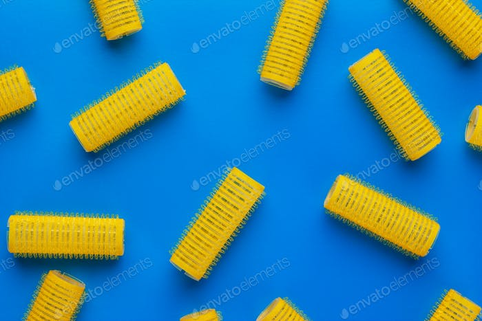 yellow hair curlers on blue background