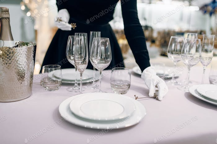 Waitress in gloves puts the knife, table setting