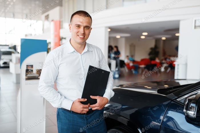 Salesman shows new car in showroom