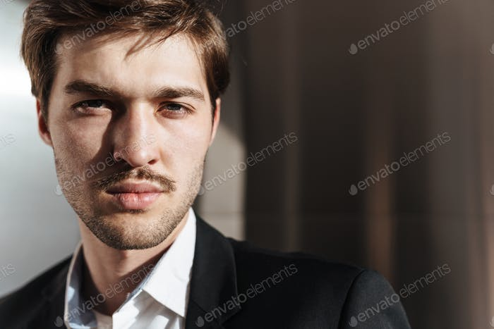 Photo of caucasian brutal businessman posing and looking at camera