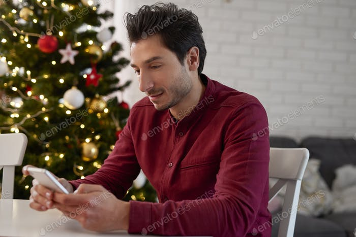 Man with mobile phone sending the best wishes for Christmas