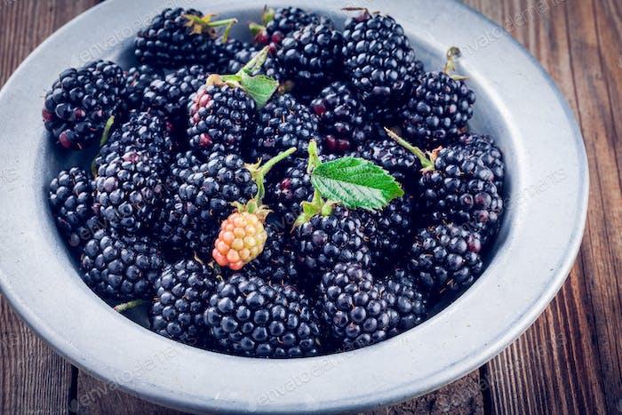 juicy fresh organic blackberries in old bowl
