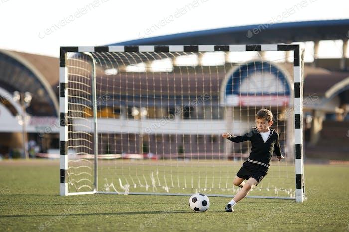 Junge spielt Fußball auf Stadion