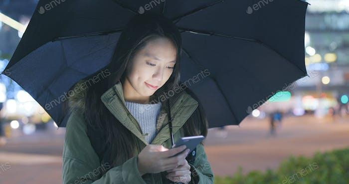 Frau Verwendung von Handy in der Stadt mit bringen Regenschirm