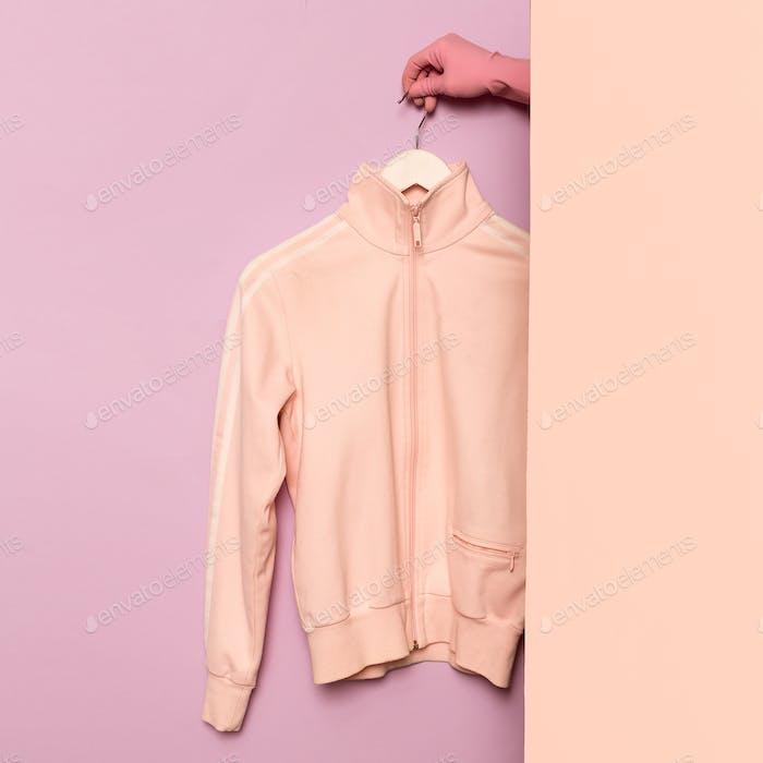 Stylish sportswear. Minimal fashion. Pink jacket on a hanger. Wa