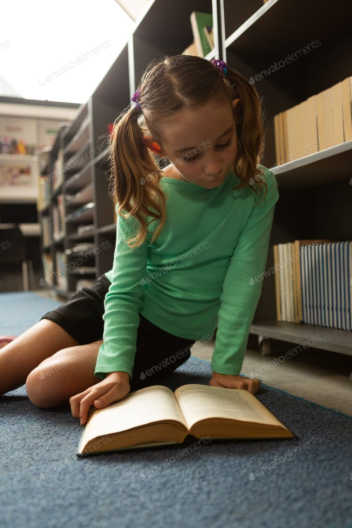 Schoolgirl sitting on floor and reading a book in library at elementary school