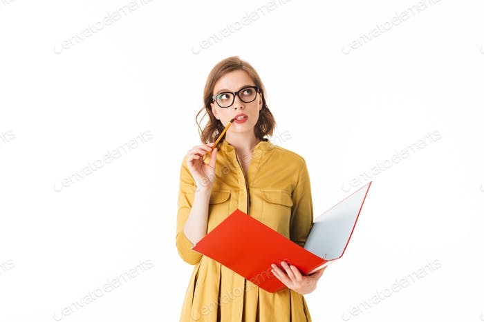 Portrait of young lady in eyeglasses standing with open red folder and pencil in hands